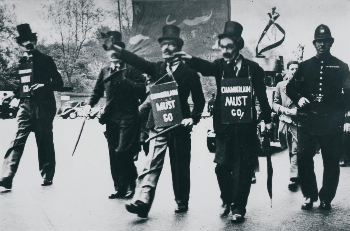 Grupa związanych z AIA brytyjskich surrealistów w maskach premiera Wielkiej Brytanii Neville'a Chamberlaina podczas parady pierwszomajowej w 1938 roku / British surrealists (among tchem members of the AIA) dressed up as Neville Chamberlain during the May Day parade in London in 1938